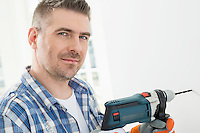 Portrait of mid-adult man drilling hole in wall