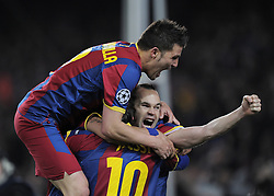 Lionel Messi of Barcelona celebrates with Andreas Iniesta and David Villa after scoring his sides opening goal during the UEFA Champions League round of 16 second leg match between Barcelona and Arsenal on March 8, 2011 in Barcelona, Spain.
