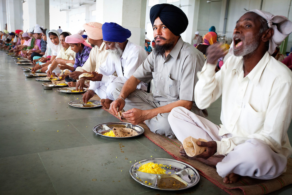 Sikh believers eating at the dinning hall of the Langar. Some Langars serve tens of thousand free meals per day. The meals are provided to all people (sikh or non sikh )without any discrimination.<br />