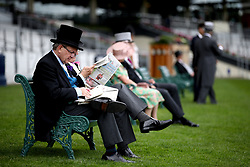 Racegoers read through newspapers during day two of Royal Ascot at Ascot Racecourse.