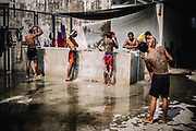 Bangkok  March 2014, inmates and Muay Thai (kickboxing) fighters, washing after a training session at the Klong Prem high-security prison. Klong-prem Central Prison, or generally called Lad-yao prison, is a high-security prison in Bangkok, taking in custody of male offenders whose sentence term is not over 25 years. With its general capacity to incarcerate offenders (5000+), the prison currently takes in custody of both Thai and foreign nationals. <br /> The inmates is part of a program that pits prisoners against foreign Muay Thai fighters or others inmates for a chance of reduced sentencing or early release. In 2012 an Estonian entrepreneur, in conjunction with Thailand's Department of Corrections, began a series of bouts arranged between Thai prisoners and Western Muay Thai fighters under the banner 'Prison Fight'. For the prisoners a victory holds the potential of time off their sentence while the Westerners fight for a small purse and personal ambition. Since the launch of 'prison fight' a number of prisons have adopted the idea, encouraging prisoners to take up boxing to fight drug abuse and to give them a purpose while incarcerated.Bangkok  Mars 2014, <br /> des d&eacute;tenus et des combattants de Muay Thai (kickboxing), se lavant apr&egrave;s une s&eacute;ance d'entra&icirc;nement &agrave; la prison de haute s&eacute;curit&eacute; de Klong Prem.. La prison centrale de Klong-prem, ou prison de Lad-yao, est une prison de haute s&eacute;curit&eacute; de Bangkok qui accueille en d&eacute;tention des d&eacute;linquants de sexe masculin dont la peine ne d&eacute;passe pas 25 ans. Avec sa capacit&eacute; g&eacute;n&eacute;rale d'incarc&eacute;ration des d&eacute;linquants (plus de 5 000), la prison accueille actuellement des ressortissants tha&iuml;landais et &eacute;trangers en d&eacute;tention. <br /> Les d&eacute;tenus font parties d'un programme qui oppose les d&eacute;tenus &agrave; des combattants &eacute;trangers du Muay Thai ou &agrave; d'autres d&eacute;t