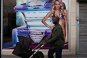 A father pushes a pushchair past a girl wearing a bikini in a high-street advert for sunbeds, on 26th December 2016, in Bristol's Broadmead, England UK