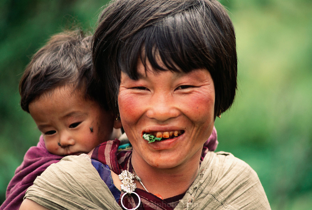 Sangay chews betel nut and lime wrapped in a leaf, which, from long-term use, has discolored her teeth and gums. Shingkhey Village, Bhutan. Nalim and her daughter Sangay care for the children and work in their mustard, rice, and wheat fields. Namgay, who has a hunched back and a clubfoot, grinds grain for neighbors with a small mill his family purchased from the government. From Peter Menzel's Material World Project.