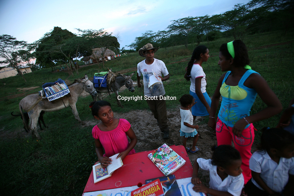 Luis Soriano, 36, brings a book from his Biblioburro, or Donkey Library, for a small group of youngsters in El Brasil, in northern Colombia on Saturday, October 11, 2008. (Photo/Scott Dalton)
