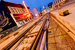 Track laying progress underway for the downtown Kansas City streetcar line. Diminishing sight-line photo from near front of Michael's Clothing Store at about 19th & Main Streets.