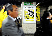 """Commuters walk past a poster requesting commuters refrain from lewd behavior on trains at an underground station in Tokyo, Japan. The Japanese are well known for their civility and politeness,  but a recent governmental campaign to clamp down on lewd behavior that may inconvenience others -- including talking on cell phones and applying makeup while commuting on a train -- was fueled by a decline in everyday etiquette and manners. The poster's headline reads """"Please do it at home."""""""