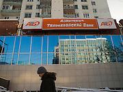 Bank Gebaeude im Zentrum der jakutischen Haupstadt Jakutsk. Jakutsk hat 236.000 Einwohner (2005) und ist Hauptstadt der Teilrepublik Sacha (auch Jakutien genannt) im Föderationskreis Russisch-Fernost und liegt am Fluss Lena. Jakutsk ist im Winter eine der kältesten Großstaedte weltweit mit durchschnittlichen Winter Temperaturen von -40.9 Grad Celsius. Die Stadt ist nicht weit entfernt von Oimjakon, dem Kältepol der bewohnten Gebiete der Erde.<br /> <br /> Man passing a bank in the city centre of Yakutsk. Yakutsk is a city in the Russian Far East, located about 4 degrees (450 km) below the Arctic Circle. It is the capital of the Sakha (Yakutia) Republic (formerly the Yakut Autonomous Soviet Socialist Republic), Russia and a major port on the Lena River. Yakutsk is one of the coldest cities on earth, with winter temperatures averaging -40.9 degrees Celsius.