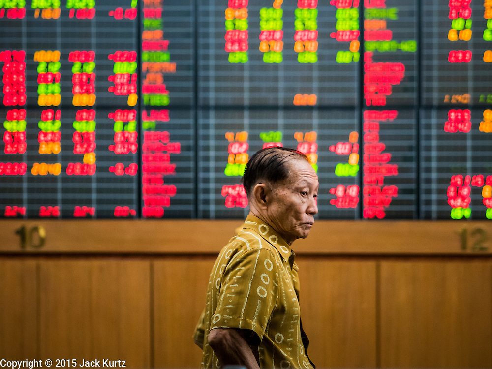 08 JULY 2015 - BANGKOK, THAILAND: A man turns away from the screens as Thai stocks drop Wednesday. Thai financial markets and the Thai Baht both lost value Wednesday. The stock market, the Stock Exchange of  Thailand (SET) closed at 1,470.25, down 13.52 or 0.91%, from Tuesday. The Thai Baht closed at 33.90 Baht to 1 US Dollar, it's lowest point since September 2009. Economists blamed the drop in the Chinese stock markets and uncertainty over the EU's handling of the Greek budget crisis for the drops in Thai markets.    PHOTO BY JACK KURTZ
