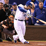 Kansas City Royals third baseman Mike Moustakas hits the ball for a double to score teammate Kansas City Royals Alex Gordon during the second inning in Game 6 of the World Series on Tuesday, October 28, 2014 at Kauffman Stadium in Kansas City, Mo.