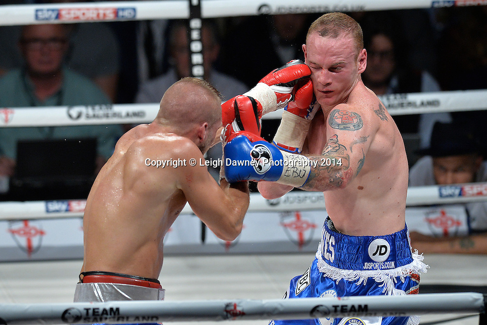 George Groves takes a left jab from Christopher Rebrasse during the EBU (European) Super Middleweight Title & Vacant WBC Super Middleweight Title at the SSE Wembley Arena, London on the 20th September 2014. Sauerland Promotions. Credit: Leigh Dawney Photography.