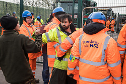 Harefield, UK. 8 February, 2020. HS2 engineers link arms to try to block environmental activists who had crawled through a ditch under a road closure implemented by HS2 engineers on Harvil Road in the Colne Valley to facilitate tree felling works for the high-speed rail project. Environmental activists based at a series of wildlife protection camps in the area prevented the tree felling works for the duration of the weekend for which they were scheduled.