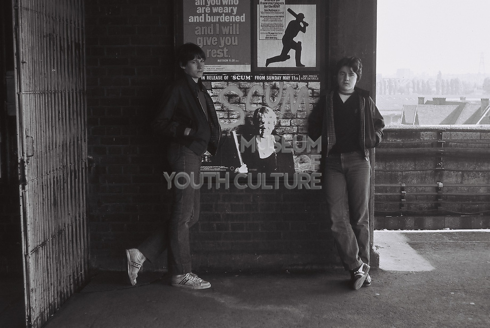 Two teenage friends stand in front of advertising poster for the film scum with Ra. London, Greenford, UK, 1980s.