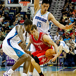 April 19, 2012; New Orleans, LA, USA; Houston Rockets point guard Goran Dragic (3) is defended by New Orleans Hornets guard Jerome Dyson (11) and power forward Gustavo Ayon (15) during the second half at the New Orleans Arena. The Hornets defeated the Rockets 105-99.   Mandatory Credit: Derick E. Hingle-US PRESSWIRE