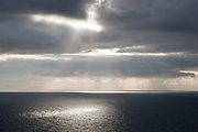 A pool of sunlight scuds across the sea off the Cornish coast.