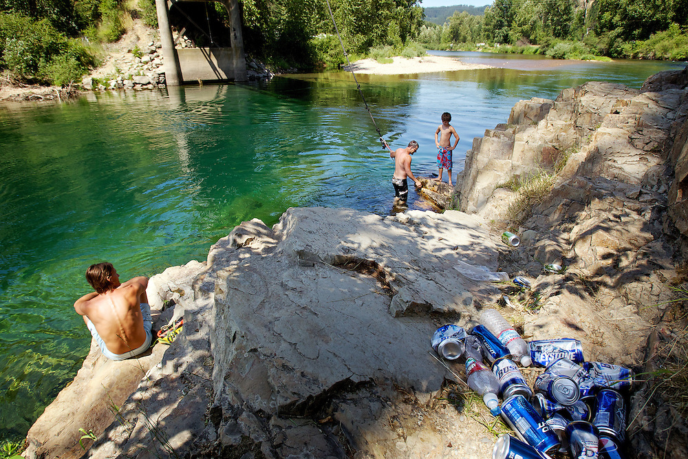 With the garbage from previous river floaters littering the rocks and shoreline along the Coeur d'Alene River, Gabriel Clark, left, Ezra Clark and Hunter Clark, 11, relax below the Old River Road bridge after playing on the rope swing Wednesday. The Shoshone County Sheriff's Department are increasing their patrols to curtail the ill effects of the influx of people who recreate on the river during the weekends.