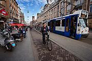 In Amsterdam passeert een fietser met een mobieltje in zijn hand op het Damrak een tram.<br /> <br /> In Amsterdam a cyclist at the Damrak passes a tram.