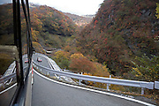 tour bus driving downhill on a mountain pass in autumn season Okunikko mountain range Japan
