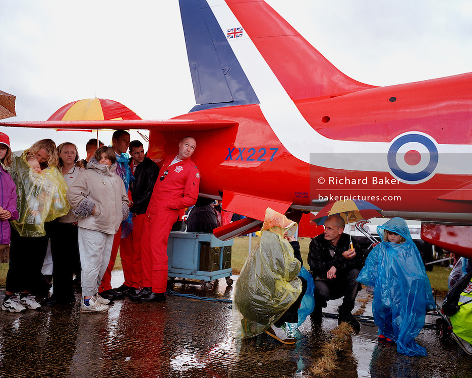Sheltering from a rain shower at the Kemble Air Day, some pilots of the elite 'Red Arrows', Britain's prestigious Royal Air Force aerobatic team, gather beneath a full-scale model of a Hawk jet aircraft. Spectators have also gathered in their waterproof wear to make a colourful group. Flight Lieutenant Steve Underwood, who as commentator and Ground Safety Manager worries about the cloud cover and the implications for a safe display. He looks towards the gloomy sky to assess the prospects of a Red Arrows show in a short while. Dressed in red flying suits, the pilots have been signing PR autographs and distributing team brochures to some of their many fans before the deluge which sent the public undercover to seek shelter. The team's main purpose is to forge a link between the RAFand potential recruits plus the general public.