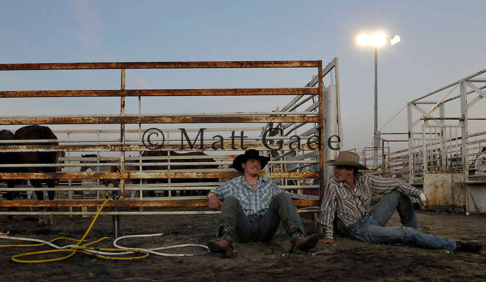 Jason Schwindt, center, of Brunswick, NE Dave Blest, of Carleton, NE, share a laugh as the pair were waiting for the bull riding competition to start during the John C. Fremont Days Rodeo on Saturday night.