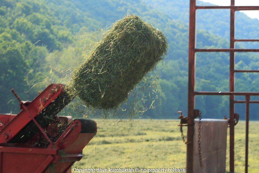 a hay baler catapults a hay bale into the wagon. no property release