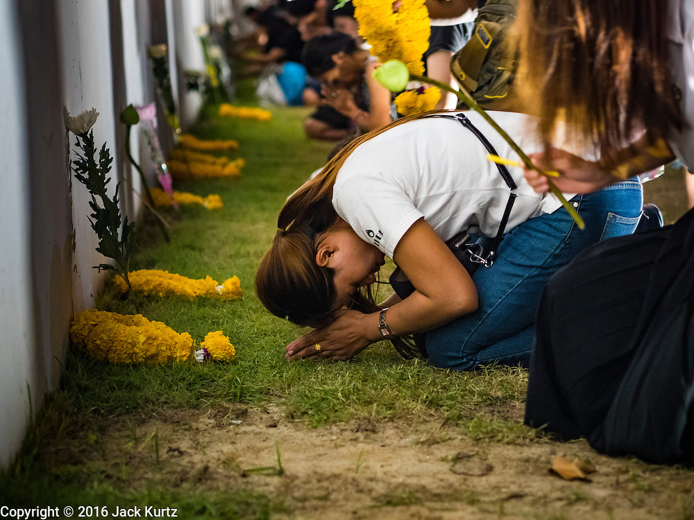 20 OCTOBER 2016 - BANGKOK, THAILAND: A woman in mourning for the death of Bhumibol Adulyadej, the King of Thailand, prays at the wall of the Grand Palace in Bangkok. Sanam Luang, the Royal Ceremonial Ground, is packed with people mourning the Monarch's death. The King died Oct. 13, 2016. He was 88. His death came after a period of failing health. Bhumibol Adulyadej was born in Cambridge, MA, on 5 December 1927. He was the ninth monarch of Thailand from the Chakri Dynasty and is also known as Rama IX. He became King on June 9, 1946 and served as King of Thailand for 70 years, 126 days. He was, at the time of his death, the world's longest-serving head of state and the longest-reigning monarch in Thai history.        PHOTO BY JACK KURTZ