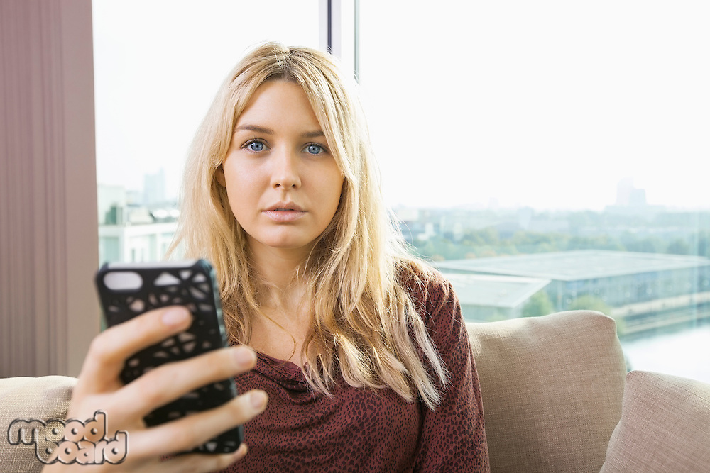 Portrait of beautiful young woman with mobile phone at home