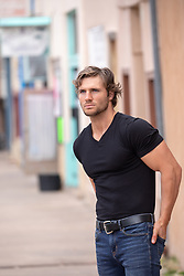 hot guy with long brown hair in a rustic town