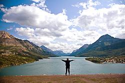 Woman celebrating huge scenery at Upper Waterton Lake, Waterton-Glacier International Peace Park World Heritage Site, Alberta, Canada.