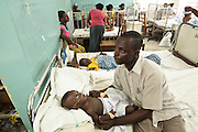 Ghana: 25 April 2012, Cephas Anane prays over his son Isiah, 9 months old, who suffers from pneumonia, as he breathes oxygen from a tank while lying on a bed at the Princess Marie Louise Children's hospital in Accra. The GAVI Alliance is a public-private partnership that brings together developing country and donor governments, WHO, UNICEF, the World Bank, the vaccine industry in both industrialised and developing countries, research and technical agencies, civil society, the Bill & Melinda Gates Foundation and other private philanthropists.  Set up in 2000 as the Global Alliance for Vaccines and Immunisation, GAVI's mission is to save children's lives and protect people's health by increasing access to immunisation in the world's poorest countries.