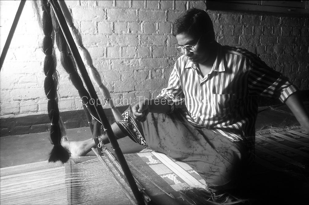 "Craftsman weaving 'Dumbara"" mats at a pit loom."