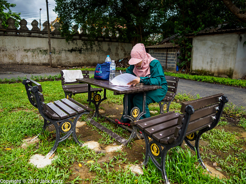 07 JUNE 2017 - BANGKOK, THAILAND:   A city worker in a new park in Pom Mahakan. Bangkok city officials are expected to tear the structure down in coming weeks. The final evictions of the remaining families in Pom Mahakan, a slum community in a 19th century fort in Bangkok, have started. City officials are moving the residents out of the fort. NGOs and historic preservation organizations protested the city's action but city officials did not relent and started evicting the remaining families in early March.         PHOTO BY JACK KURTZ