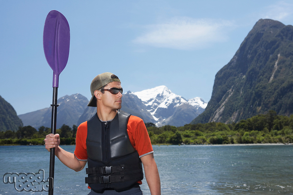 Man holding oar on shore of mountain lake