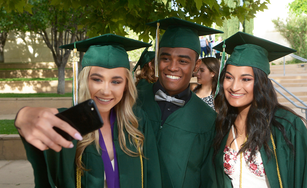 gbs051817g/ASEC -- DeShawn Lee , center, gets selfie with Shea Auge, left, and Tiana Castillo before Hope Christian High School graduation ceremonies at Calvary Albuquerque Church on Thursday, May 18, 2017. (Greg Sorber/Albuquerque Journal)