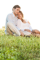Relaxed couple with eyes closed sitting on grass in park