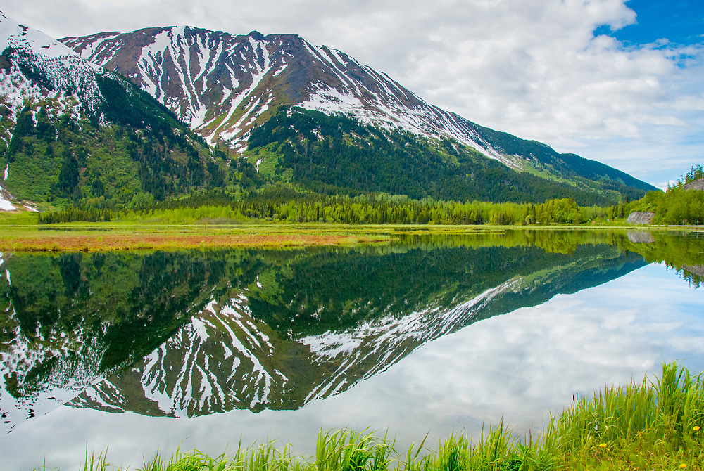 A flat lake perfectly mirrors the image of a breathtaking mountain landscape.