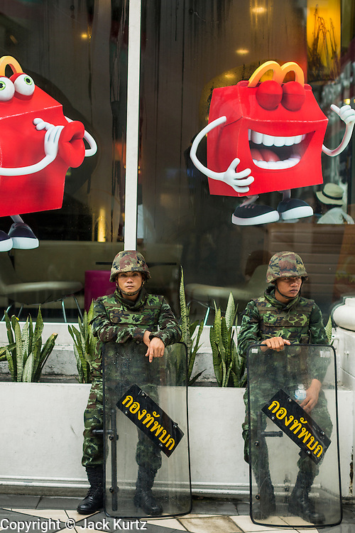 25 MAY 2014 - BANGKOK, THAILAND: Thai soldiers relax in front of a McDonald's fast food restaurant in Bangkok in anticipation of large anti-military rally. Public opposition to the military coup in Thailand grew Sunday with thousands of protestors gathering at locations throughout Bangkok to call for a return of civilian rule and end to the military junta.     PHOTO BY JACK KURTZ