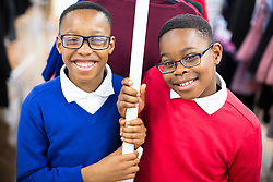 © Licensed to London News Pictures . Manchester , UK . WISDOM UDENSI (11) and his brother DIVINE UDENSI (nine) (both correct) (from Moston) in new school uniforms at the shop . The Wood Street Mission is opening its community shop today (Tuesday 16th August 2016) , enabling families on a low income to get school uniform and other school necessities for free , in time for the new school year . Founded by Methodist Minister Alfred Alsop in 1869 , the Mission's aim is to alleviate the effects of poverty on children and families in Manchester and Salford . Photo credit : Joel Goodman/LNP