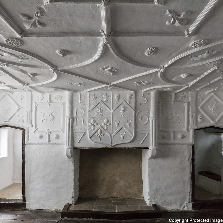 Fireplace in Robert Wynn's bedchamber featuring three severed heads of Englishman in the plasterwork, Plas Mawr, Conwy.