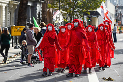 © Licensed to London News Pictures. 09/10/2019. LONDON, UK.  Members of the Red Brigade, supporters of Extinction Rebellion's demonstration, walk silently down Whitehall during day 3 of Extinction Rebellion's climate change protest in the capital.  Some of the activists had used glued themselves to the road.  Photo credit: Stephen Chung/LNP