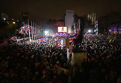 © Licensed to London News Pictures. 31/01/2020. London, UK. A statue of Britain's wartime leader Winston Churchill looms over people as they gather in Parliament Square to celebrate the United Kingdom's departure from the European Union. Photo credit: Peter Macdiarmid/LNP