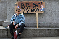 "London, April 16th 2016. A youngster sits in front of a discarded banner after thousands of people supported by trade unions and other rights organisations demonstrated against the policies of the Tory government, including austerity and perceived favouring of ""the rich"" over ""the poor""."