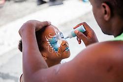 "Alexis Wood, 5, gets her face painted by Ray Parris.  ""Alvin's Cultural Workshop"" Cultural Fair honoring Mr. Alvin Turnbull.  Emancipation Garden.  St. Thomas, VI.  29 April 2015.  © Aisha-Zakiya Boyd"