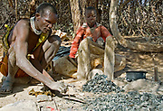 Local blacksmith of Datoga Tribe and his children working in the shade of an Acasia tree.  Lake Eyasi, northern Tanzania.