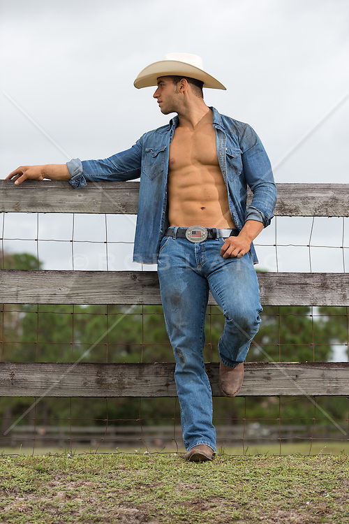 good looking sexy cowboy with an open shirt leaning against a fence on a ranch