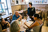 "NAPLES, ITALY - 12 SEPTEMBER 2018: Giusy Aiese, co-owner of the Taverna del Buongustaio, takes orders from customers, in Naples, Italy, on September 12th 2018.<br /> <br /> Taverna del Buongustaio was founded in the 1930s by wine producer of the province of Caserta. Gaetano Aiese and his daughter Giusy have been managing the tavern since 1996. Customers of the Taverna are professors of the nearby University, students, merchants and employees of via Toledo, the commercial street right around the corner. Giusy and her father Gaetano decided to invest in the traditional Neapolitan cuisine. ""I learned cooking from my dad. And my dad learned cooking from his mother"", Giusy said."