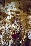 "People on a walkway admire Caverns of Sonora, Sutton County, Texas, USA. The world-class Caverns of Sonora have a stunning and sparkling array of speleothems (helictites, stalactites, stalagmites, flowstone, coral trees, and other calcite crystal formations). National Speleological Society co-founder, Bill Stephenson said, after seeing it for the first time, ""The beauty of Caverns of Sonora cannot be exaggerated...not even by a Texan!"" Geologically, the cave formed between 1.5 to 5 million years ago within 100-million-year-old (Cretaceous) Segovia limestone, of the Edward limestone group. A fault allowed gases to rise up to mix with aquifer water, making acid which dissolved the limestone, leaving the cave. Between 1 and 3 million years ago, the water drained from the cave, after which speleothems begain forming. It is one of the most active caves in the world, with over 95% of its formations still growing. Sonora Caves are on Interstate 10, about half-way between Big Bend National Park and San Antonio, Texas."