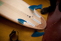 Danny Hess, who specializes in making surfboards out of sustainable wood, adds fins to his surfboard before heading out to the beach, in San Francisco, Ca., on Wednesday, July 6, 2011.