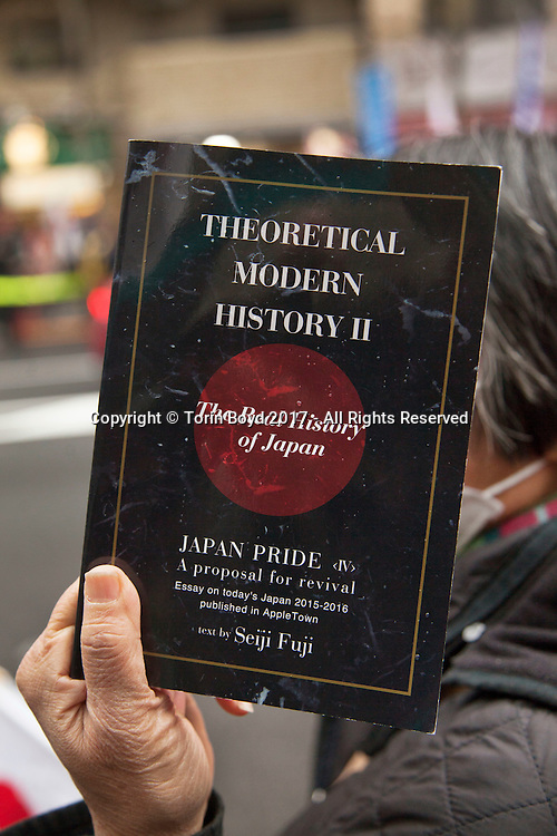 "February 5, 2017, Tokyo, Japan: An ultra-right winger demonstrating in front of APA Hotel's Shinjuku Gyoenmae branch, holds up a copy of Toshio Motoya's history revisionist book. This highly controversial book will be pulled from all APA Hotel rooms hosting athletes of the 2017 Sapporo Asian Winter Games, much to the ire of Japanese nationalists. The book in question written by Toshio Motoya, the hotel chain's Chief Executive, claims the 1937 Nanjing Massacre was a fabrication. Writing under the pen name Seiji Fuji, Motoya's book entitled ""Theoretical Modern History II"" is placed in every APA Hotel room in Japan and sold at their reception desks. The Tokyo based APA Hotel group is one of the largest hotel chains in Japan with over 400 hotels across the country. In the past 2-3 years APA has benefitted from a tourism boom to Japan in which 40% of their guests are foreign visitors and half that amount are Chinese and Korean nationals. As a result, China and Korea have been outraged by APA and a large boycott began in late January by both countries. This led to APA announcing they would pull Motoya's books from athlete's rooms only during the Asian Winter Games, infuriating Japanese right wingers. The demonstrators at this event are part of a group who call themselves ""Group of Warriors Protecting the Nation"" (Gokoku Shishi no Kai). Photo by Torin Boyd."