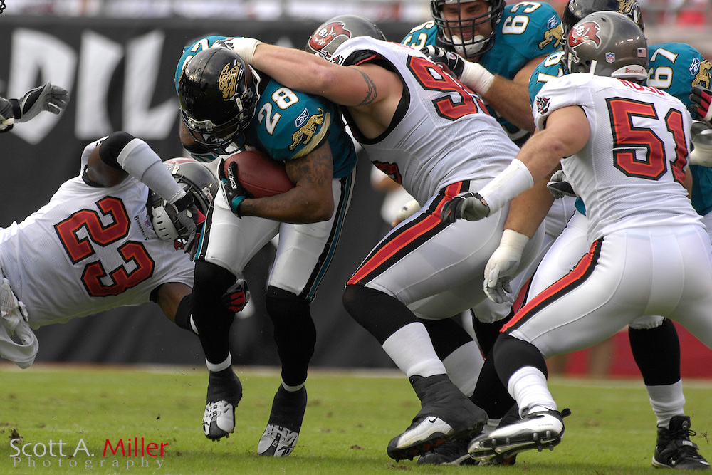 Jacksonville Jaguars running back (28) Fred Taylor is tackled by Tampa Bay Buccaneers defender (95) Chris Hovan and defender (23) Jermaine Phillips during the first half at Raymond James Stadium on Oct. 28, 2007 in Tampa, Florida.       ..©2007 Scott A. Miller