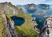 Above the Arctic Circle, ascend a slippery steep trail to Reinebringen for spectacular views of Reine village and sharply glaciated peaks surrounding Reinefjord, on Moskenesøya (the Moskenes Island), Lofoten archipelago, Nordland county, Norway. Panorama stitched from 4 overlapping photos.